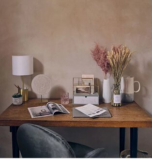 Pink room with wooden-effect table topped with open books, gold-effect white storage lamp, artificial plant, gold-effect storage box, white ribbed vase with pink artificial plant and cream and grey jug.