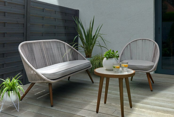 Patio with light grey wicker wooden-effect garden sofa set with two iced drinks and an artificial plant.
