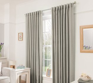 Sage green curtains hanging from silver rail in a decorated white room
