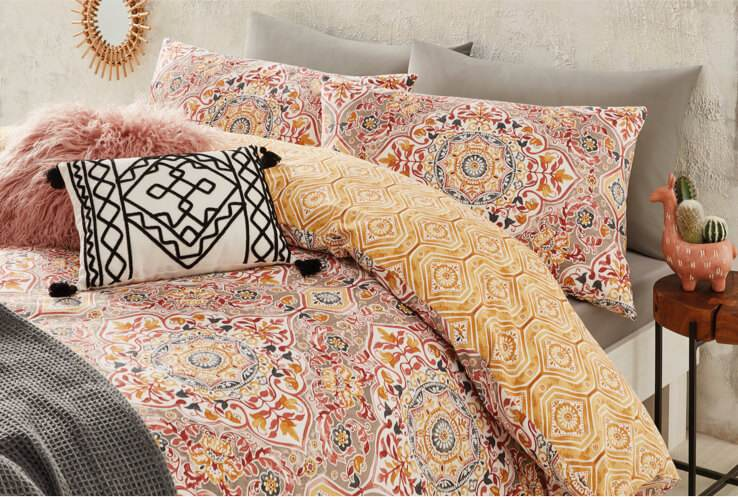 Multi-coloured patterned bedsheets with grey cushions decorated with a black and white tribal cushion