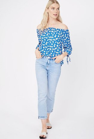 Woman wearing a blue off the shoulder top with light wash straight cut jeans and sliders