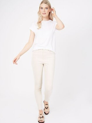 Woman wearing a white t-shirt with cream lightwash skinny jeans and strappy sandals