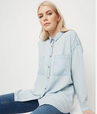 Woman wearing a light wash denim longline shirt with dark wash jeans