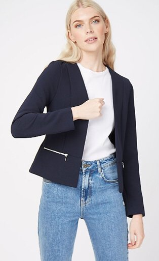 Woman wearing a white t-shirt, navy zip detail blazer and mid wash jeans