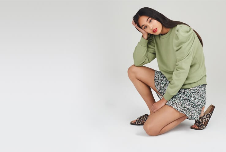 Woman kneeling wearing a green top, ditzy floral skirt and leopard print sandals