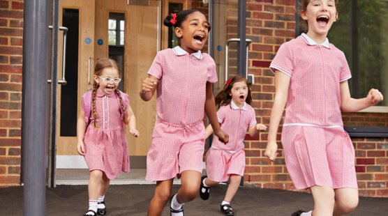 Four girls wearing red gingham dresses smiling and running out of school
