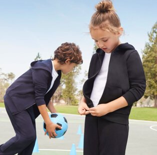 A girl and boy wearing navy joggers, zip up hoodies and white t-shirts, playing with a blue football in a playground