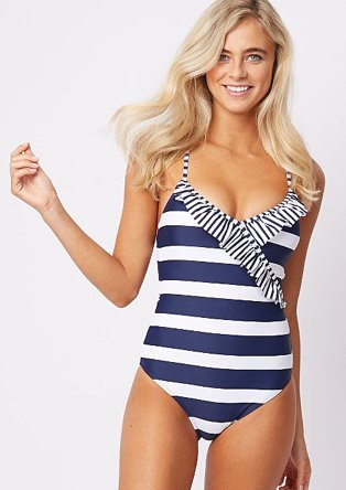 Woman wearing a navy and white stripe swimsuit with thrilling around the straps