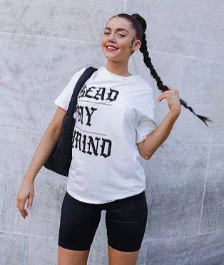 Woman poses smiling holding end of ponytail wearing white read my mind slogan t-shirt, black cycling shorts and black handbag.