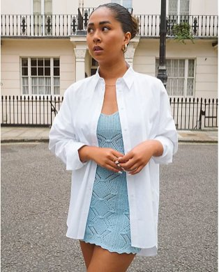 Woman poses looking away from camera wearing white oversized shirt over blue mini dress.