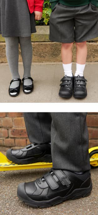 Legs of girl wearing grey skirt, grey tights and black patent 1 strap ballet shoes next to legs of boy wearing grey shorts, white socks and black 2 strap school shoes. Close up shot of boys feet wearing black 2 strap school shoes with one foot raised on yellow scooter.
