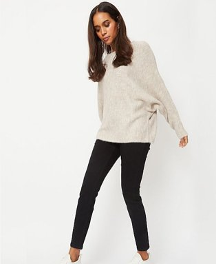 Woman wearing a beige jumper with black jeans and white trainers.