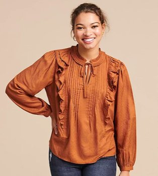 Woman poses smiling with hand on hip wearing tan textured frill tie neck blouse.