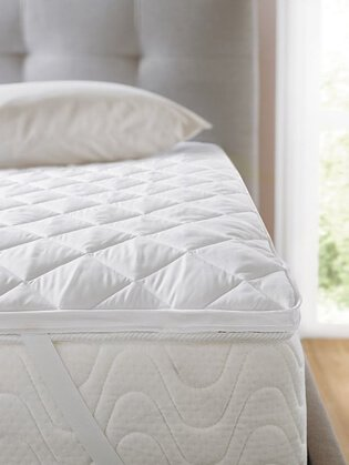 Double bed with grey quilted headboard, white mattress with mattress protector and pillow.