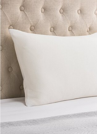 Section of bed with natural colour quilted headboard, white pillow and sheet with grey throw.