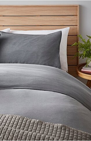 Section of bed with wooden headboard, grey bedding and textured grey throw with wooden bedside table with plant.
