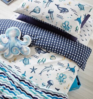 Layers of blue and white bedding printed with sea creatures and polka and stripey patterns with octopus cushion.