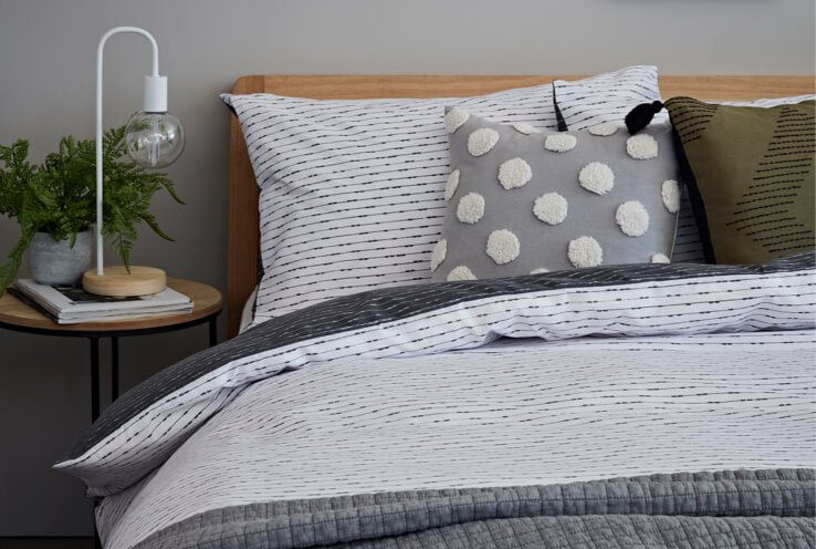Double bed with wooden headboard with white printed duvet cover, grey throw and spot and stripe printed scatter cushions next to table with wire bulb table lamp and plant.