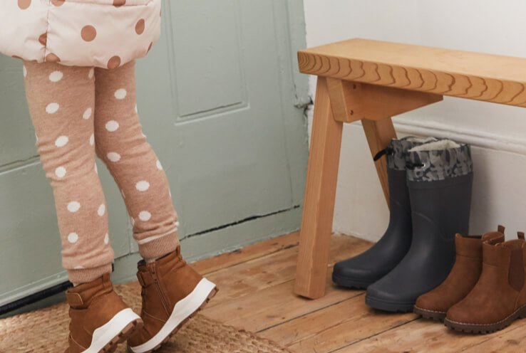 Legs of girl wearing pink polka dot leggings and coat next to green door and wooden table with adult grey wellington boots and kids' brown ankle boots underneath.