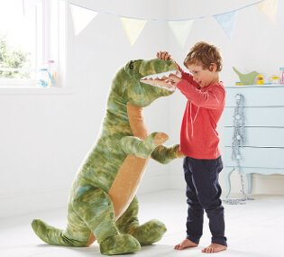 A boy in a red jumper and dark trousers in a playroom playing with a large plush T-Rex dinosaur toy.
