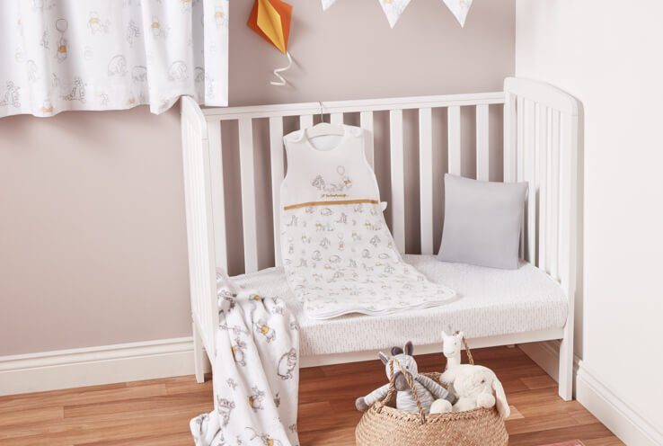 White cot with a white mattress and grey pillow, a white grey and yellow sleepsuit on a hanger and a basket of plush toys on the floor.