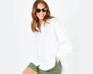 Woman poses smiling wearing white step hem shirt, khaki shorts and brown tortoiseshell effect sunglasses.