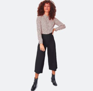 Woman poses with hand on hip wearing pink polka dot printed shirt, black Ponte culottes and black ankle boots.