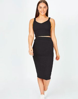 Woman poses smiling wearing black ribbed co-ord midi skirt and crop top and white trainers.