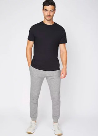 Man poses wearing black t-shirt, grey marl jersey joggers and white trainers.