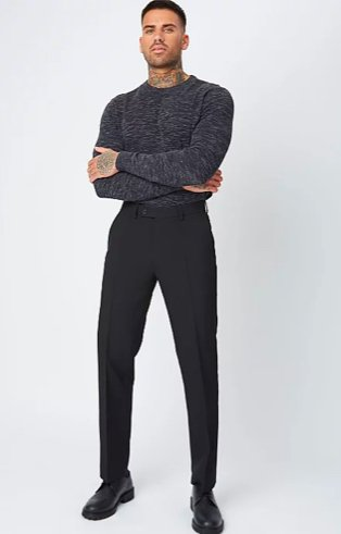 Man poses wearing black marl lightweight jumper tucked into black regular fit trousers and wide fit black leather lace-up oxford shoes.