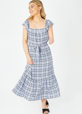 Woman poses looking over shoulder wearing blue check print square neck midi sundress and black sandals.