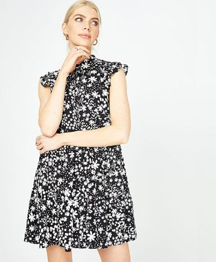 Woman poses smiling wearing black floral print tiered sleeveless shirt dress.