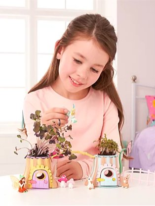 Young girl sits at white table playing with my fairy unicorn garden.