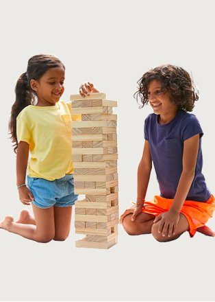 Boy and girl sit on floor playing with large Jenga game.