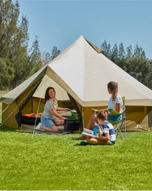 Large green space features smiling woman opening picnic cooler inside Ozark Trail olive green yurt tent 8 person with teenage girl sat on chair and young boy sat on grass.