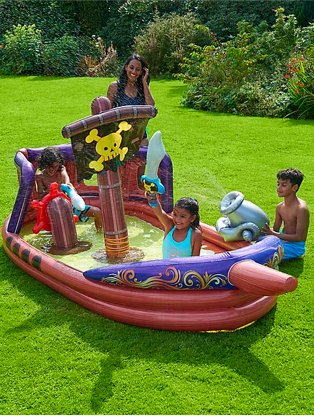 Garden features woman watching young girl and young boy playing on inflatable pirate ship.