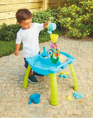 Gated garden features young boy playing with kid connection sand and water activity table.