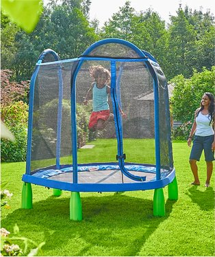 Garden features woman smiling watching young girl jumping on 7FT my first trampoline.
