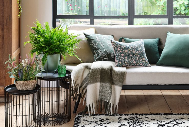 Cream sofa with assorted green floral scatter cushions, grey and cream plaid throw with large artificial plant on one side.