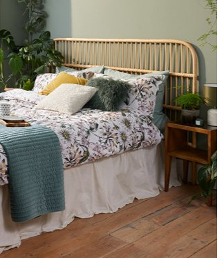 Double bed with floral bedding, green, cream and yellow scatter cushions, cream valance, green textured throw with wooden side table.
