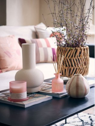 Cream sofa with pink, beige and cream scatter cushions, matte black coffee table with large wicker artificial plant, white vase, pink and white stripe vase, pink candle and reed diffuser.
