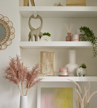 White shelf with giraffe ornament, rainbow artificial plant, pink candle and diffuser and artificial trailing plant, white shelf with bamboo lamp, pink candle, white vase and elephant artificial plant next to wall with round mirror and pink artificial plant in white vase.