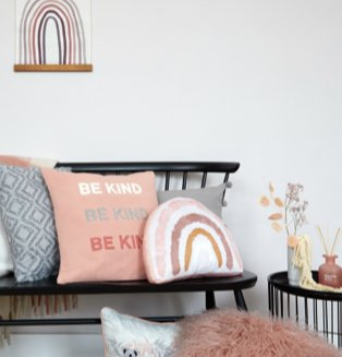 Black seat with rainbow cushion, slogan cushion and blue tile cushion next to matching black side table topped with artificial flowers and reed diffuser.