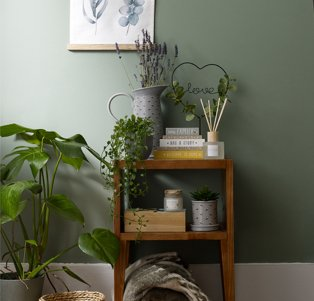 Wooden table topped with grey jug vase, 3 stacked books, reed diffuser, love wire sign and artificial trailing plant next to large artificial plant in grey pot.