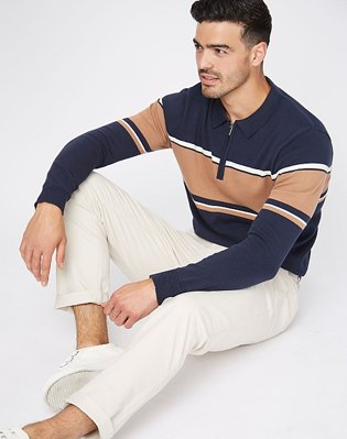 A man sitting on the floor wearing a navy striped zip polo jumper with cream trousers and white trainers.