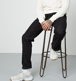 A man sitting on a bar stool wearing black straight fit jeans, a white jumper and white trainers.