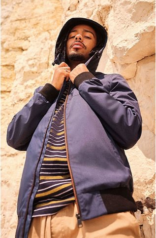 Man posing in front of a large rock wall wearing a navy bomber jacket over a navy and yellow stripe t-shirt and tan trousers.