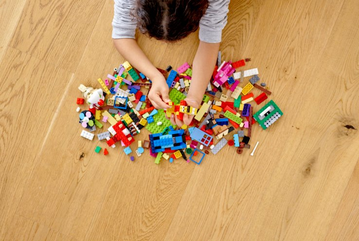 Bird's-eye view of head of child playing with LEGO on wooden floor.