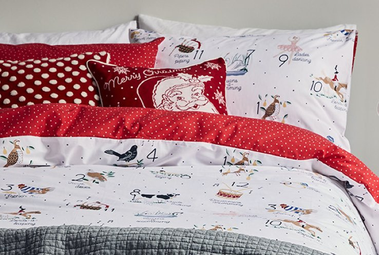 Close up of a double bed with 12 days of Christmas bedding, red and white Christmas scatter cushions and grey textured throw.