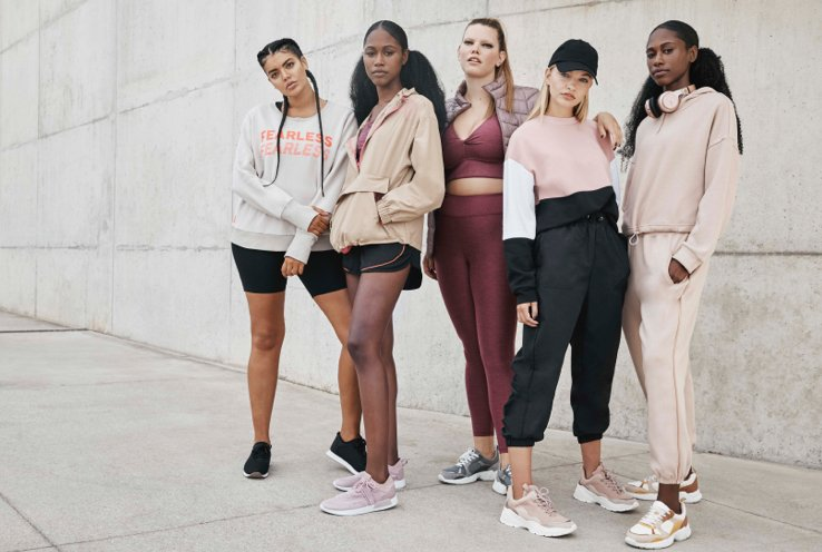 A group of women standing in front of a concrete wall wearing different sports, active and athleisure outfits.